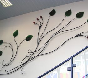 metal and glass sculpture of leaves and seed pods winding up staircase wall
