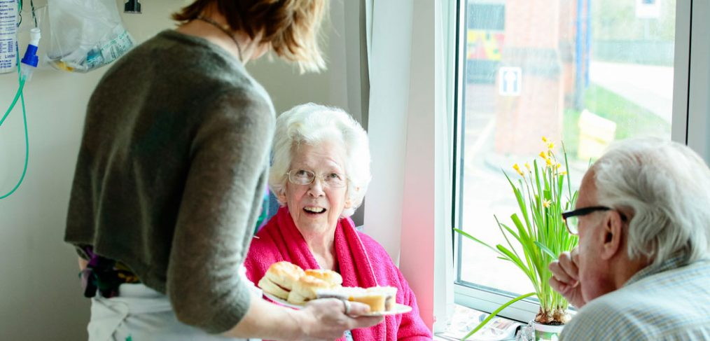 Serving scones to patients at table on ward