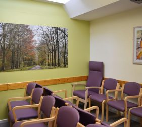 Close up view of large scale artwork of avenue of trees at end of waiting area, with lilac seating in front
