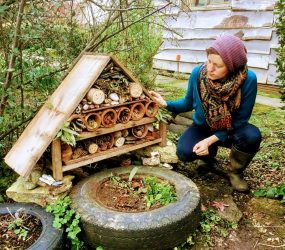 Hannah looks at her wooden hut shape filled with logs with holes drilled in, flower pots with twigs, leaves and pine cones to hide in