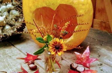 pumpkin with heart shape carved out, conkers, leaves and a posy of flowers and stems in a jam jar