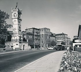View of front of Infirmary, double decker bus passing in front