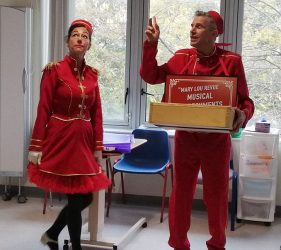 Performers dressed in red as ushers on the ward