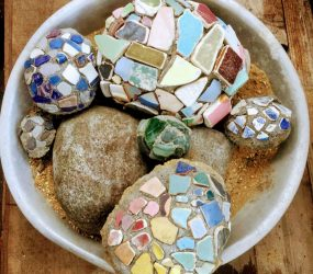 pebbles covered in worn multi-coloured pottery