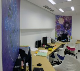 Abstract liver cell design artworks on wall behind desks