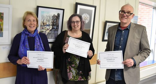 Mary Fawcett, Joanne Tudor and Fred Fieber holding certificates in front of the exhibition