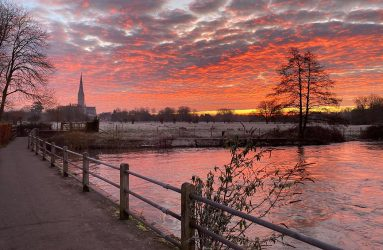 photo of pink sunrise behind silhouette of Salisbury Cathedral viewed across water meadows