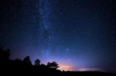 photo of silhouette of trees on hillside with backdrop of starry deep blue sky and faint golden sunlight on horizon