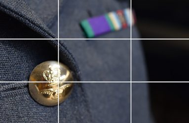 close up of brass uniform button on lower third of photo