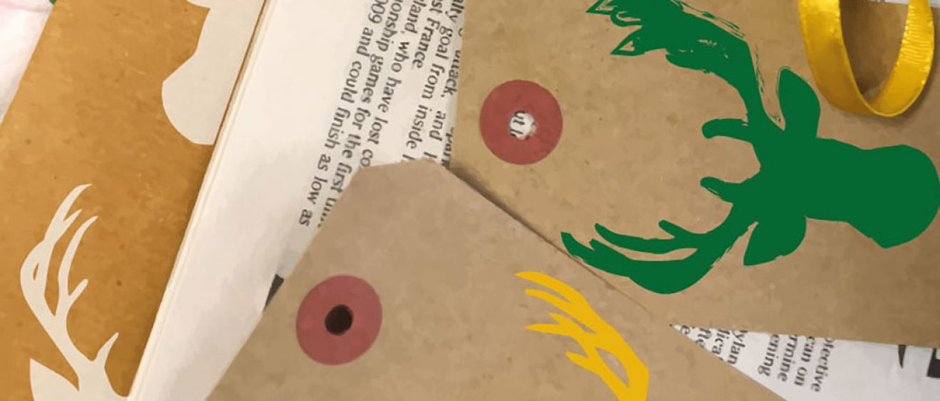 yellow and green stag's head printed onto brown card tags and brown paper