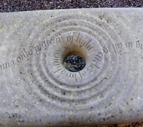 Close up of stone bench with hold and ripple effect carved stone with poetry