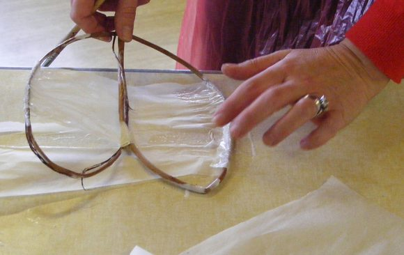 Staff member applying tissue paper to willow heart shape