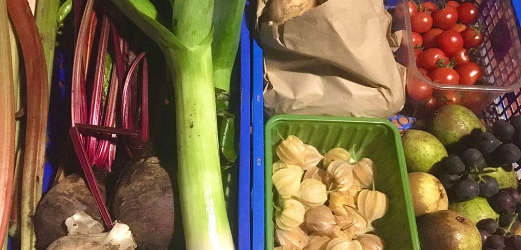 crate filled with leeks, beetroot, tomato, physalis, grapes, pears, rhubarb and potatoes