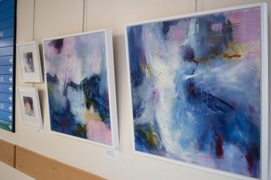 abstract blue and purple canvas hanging on wall