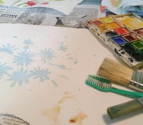 brushes, toothbrush, palette, paper and daisy outline in masking fluid