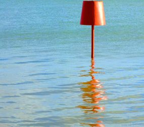 red bouy reflecting on surface of sea