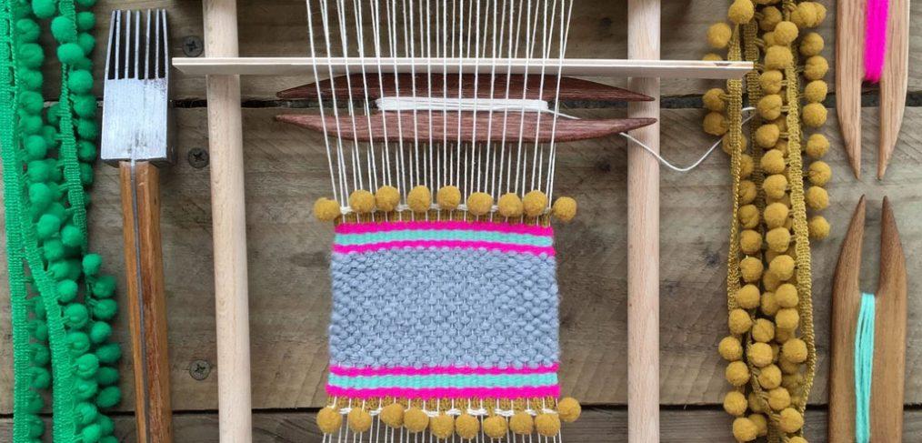 loom with weaving in progress, balls of wool surrounding