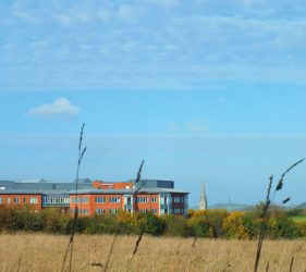 Hospital buildings, Salisbury Cathedral spire in background, fields in foreground