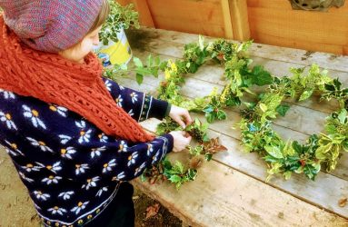 Hannah in winter woollies putting finishing touches to wreaths made from leaves and berries